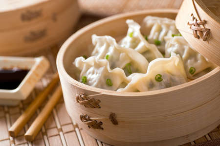Dim sum with leeks, meat, and green onions in a bamboo steamer.