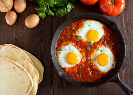 egg white: Shakshuka with eggs, tomato, and parsley in a cast iron pan.