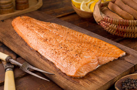 A delicious cedar planked salmon with lemon, pepper, and seasoning.