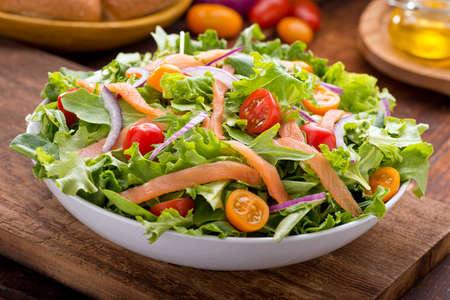 A delicious smoked salmon garden salad with smoked salmon, mixed baby greens, red and yellow cherry tomatoes and red onion with balsamic vinaigrette.