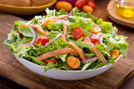 salmon ahumado: Un delicioso salmón ahumado ensalada de salmón ahumado, verduras tiernas mixtas, tomates cherry rojo y amarillo y cebolla roja con vinagreta de balsámico.