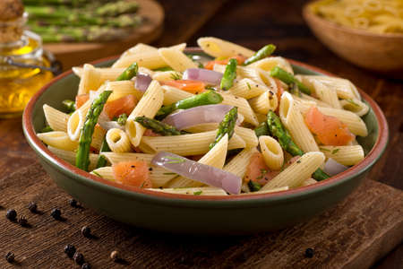 A delicious smoked salmon pasta with penne, asparagus, crushed black pepper, olive oil, and dill.