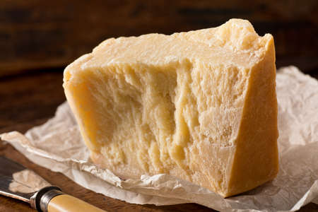 An aged authentic parmigiano reggiano parmesan cheese with wrapper and cheese knife.