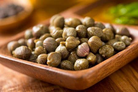 Capperi marinati in una ciotola di legno che serve con basilico e pepe nero in grani.