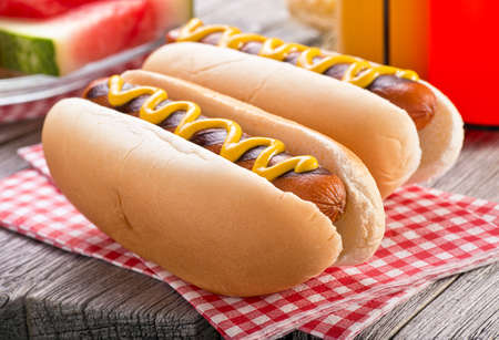 hotdog: Delicious barbecued hot dogs on a rustic picnic table.