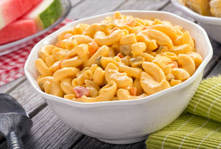 corn salad: A bowl of delicious creamy macaroni and cheese salad on a rustic picnic table with watermelon and corn. Stock Photo