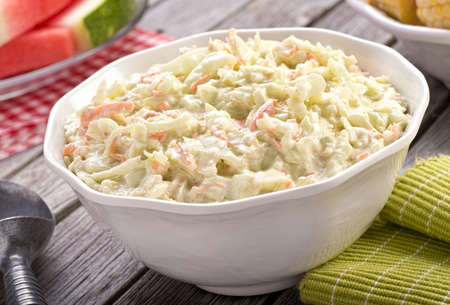 A bowl of delicious creamy homemade coleslaw on a rustic picnic table with watermelon and corn. Stockfoto