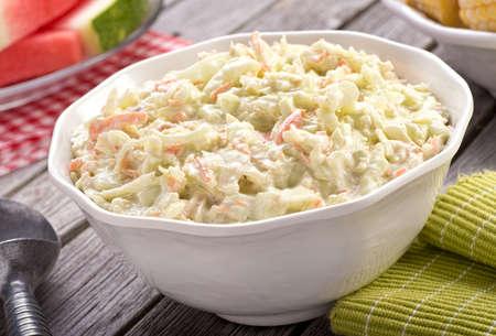 maíz: Un plato de deliciosa ensalada de col casera cremosa en una mesa de picnic r�stico con sand�a y ma�z. Foto de archivo