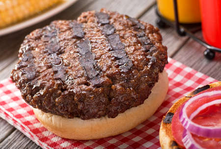 grill: A juicy barbecued hamburger with grill marks on a rustic picnic table with tomato onion mustard ketchup and corn.