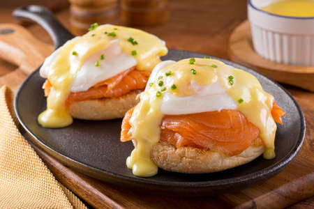 breakfast eggs: A delicious eggs benedict with smoked salmon hollandaise sauce and chives.