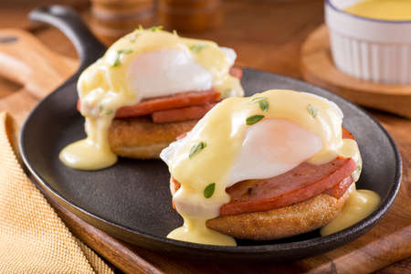 A delicious eggs benedict with thick cut ham hollandaise sauce and thyme garnish. Stockfoto