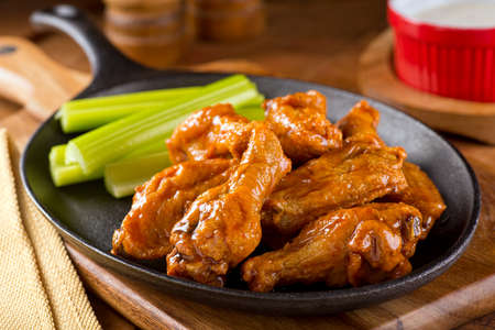 A plate of delicious Buffalo style chicken wings with celery and dipping sauce.