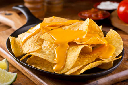 cheese plate: A plate of delicious plain nacho corn chips with cheese sauce.