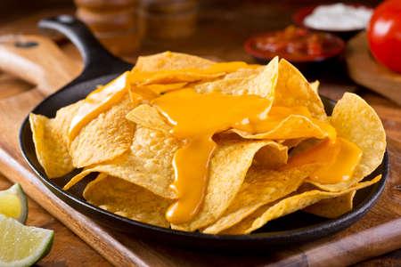 queso: Un plato de deliciosos chips de maíz nacho lisos con salsa de queso.