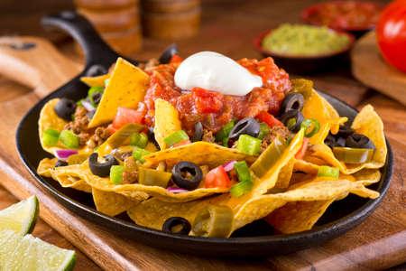 tortilla de maiz: Un plato de deliciosos nachos tortilla con salsa de queso derretido chiles jalapeños carne picada de cebolla roja cebolla verde tomate aceitunas salsa negro y crema agria con salsa de guacamole. Foto de archivo