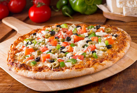 A delicious freshly baked greek pizza with feta cheese olives tomato and green pepper.