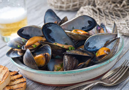 A bowl of delicious steamed mussels with grilled bread and beer on a rustic tabletop with fish net. Imagens