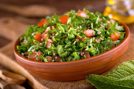 A bowl of delicious fresh tabouli with parsley, mint, tomato, onion, olive oil, lemon juice, and bulgar wheat. Stockfoto