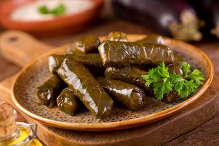 mediterranean cuisine: A plate of delicious stuffed grape leaves with parsley garnish. Stock Photo