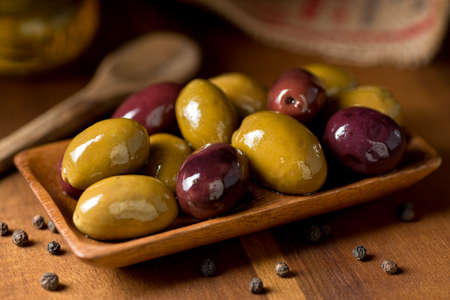 A bowl of delicious mixed olives on a rustic tabletop. Фото со стока