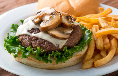 mushroom: A delicious hamburger topped with swiss cheese and fried mushrooms on a kaiser.