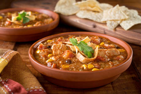 A bowl of delicious home made chicken tortilla soup with chicken, corn, black bean, tomato, hominy, and tortilla.