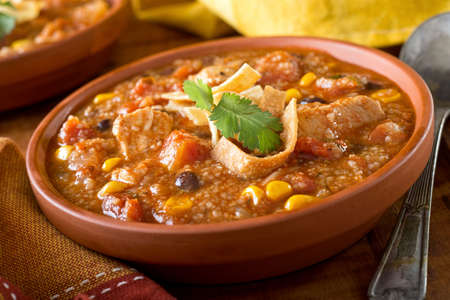 sopa: A bowl of delicious home made chicken tortilla soup with chicken, corn, black bean, tomato, hominy, and tortilla.