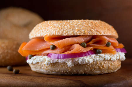 sandwich spread: A delicious homemade sesame seed bagel with smoked salmon, whipped cream cheese, red onion, and capers.