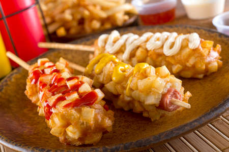 Deliciosos estilo coreano perros de maíz con trozos crujientes con pasta y patatas fritas. Foto de archivo