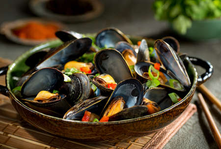 Delicious asian style steamed mussels with red pepper, green onion, and coriander in a coconut broth. Archivio Fotografico
