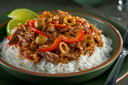 A delicious cuban ropa vieja stew on a bed of rice with lime garnish.
