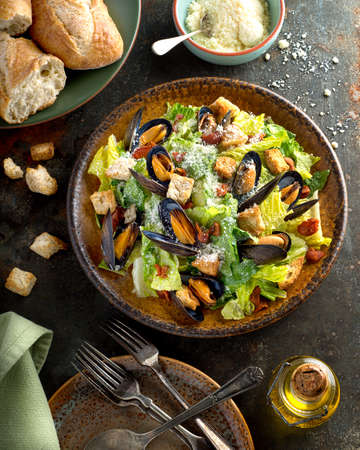 romaine lettuce: A delicious caesar salad with mussels, romaine lettuce, bacon, croutons, and parmesan cheese.