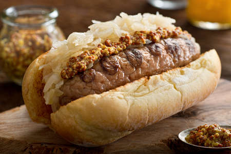 A delicious grilled sausage with sauerkraut and coarse mustard on a toasted hot dog bun. Stock Photo