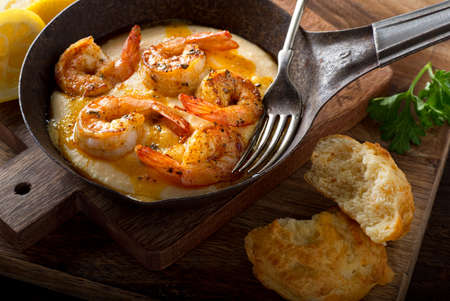 creole: A pan of delicious fresh homemade cajun style shrimp and grits with cheddar biscuit. Stock Photo