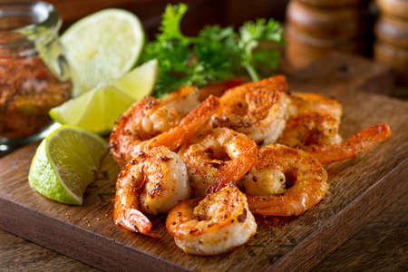 Delicious sauteed shrimp with cajun seasoning and lime on a maple plank. Reklamní fotografie - 63047556