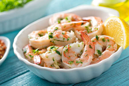 A delicious bowl of shrimp scampi with garlic, butter, and parsley. Archivio Fotografico