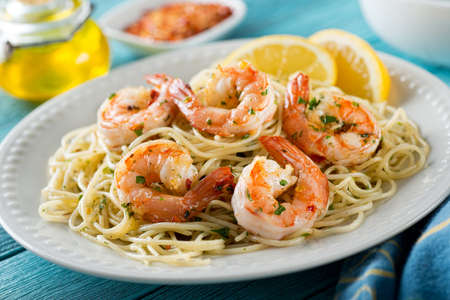 A delicious plate of shrimp scampi with spaghetti and lemon. Stock Photo
