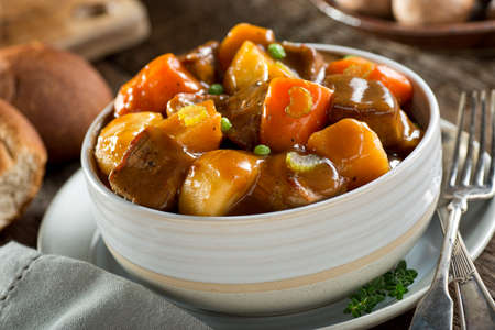 A delicious bowl of rich and hearty beef stew with potato, turnip, carrot, celery, and peas.