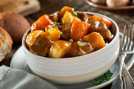 Lahodné misku bohaté a vydatné dušené hovězí s brambory, tuřín, mrkev, celer, a hráškem. Reklamní fotografie