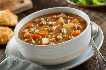 A bowl of delicious beef and barley soup with carrots, tomato, potato, celery, and peas. Stockfoto