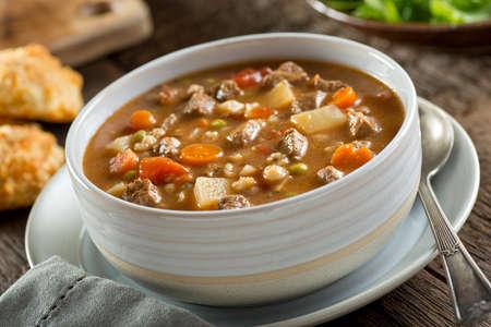 Un plato de deliciosa carne de sopa de cebada con zanahorias, tomate, patata, apio y guisantes.