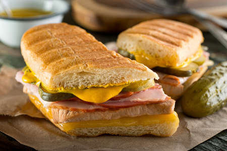 An authentic cuban sandwich on pressed medianoche bread with pork, ham, cheese, pickle, and mustard. Foto de archivo
