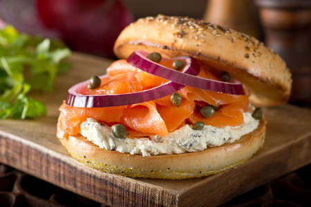 A delicious toasted bagel with smoked salmon, cream cheese, capers, and red onion. Фото со стока