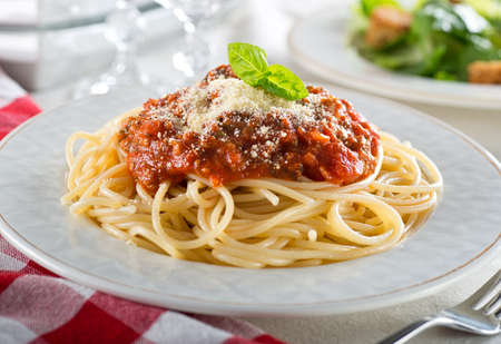 A plate of delicious spaghetti bolognese with meat sauce and fresh basil. Stock Photo