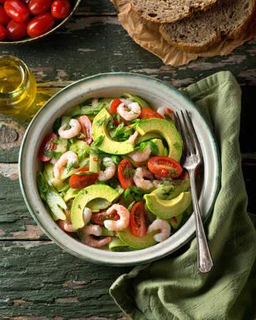 A delicious coldwater shrimp and avocado salad with tomato, cucumber, celery, green onion, cilantro, and dill.