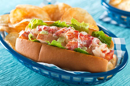 A delicious lobster roll with lettuce, celery, mayonnaise, and potato chips.