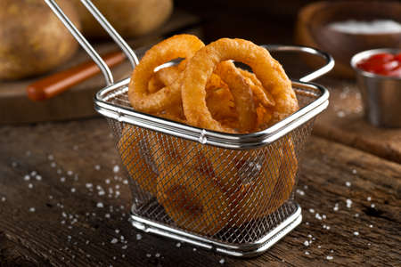 Crispy delicious onion rings in a fryer basket. Imagens