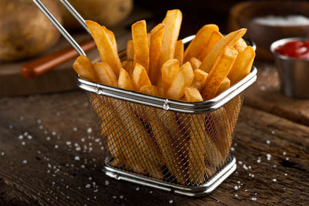 russet potato: Crispy delicious french fries in a fryer basket.
