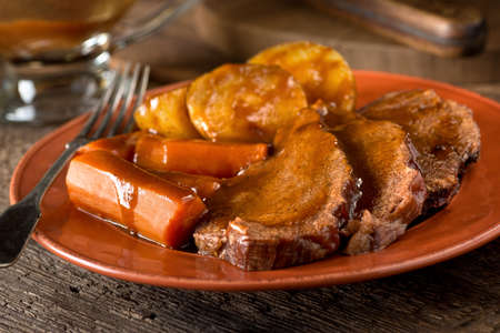 A delicious homemade pot roast dinner with potatoes, carrots, and gravy. 스톡 콘텐츠