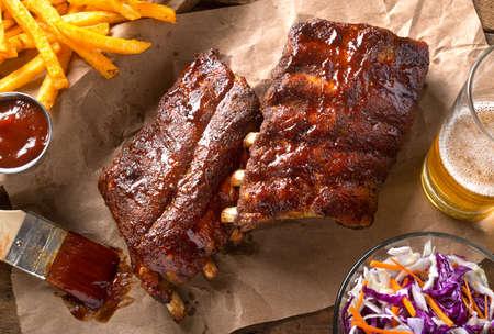 Un carré de délicieuses côtes levées avec sauce barbecue, frites, salade de chou et bière. Banque d'images